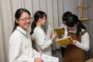 中学生の生徒たちが笑いながらアクティビティをしています。