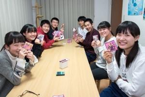 中学生の生徒たちがカードを持って笑っています。